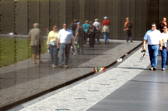 Polished black granite walls reflects the images of visitors, trees and monuments.