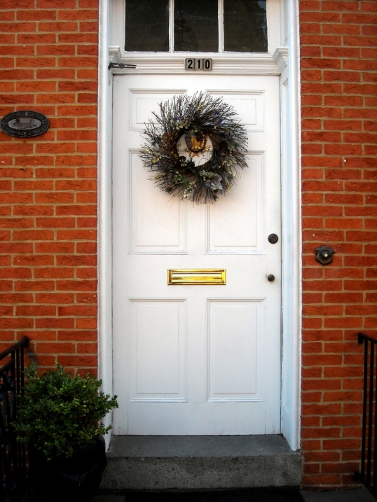 The crisp white door beautifully offsets the brick exterior.
