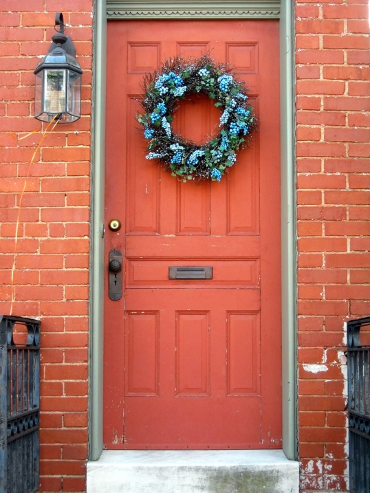 Love how the blue wreath provides contrast against the burnt orange door.
