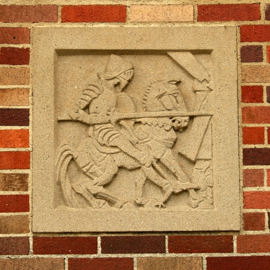 Several plaques are inset into the brick on both side of the entrance.