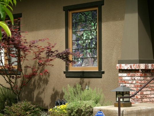 The maple tree provides nice contrast to the stained glass window.